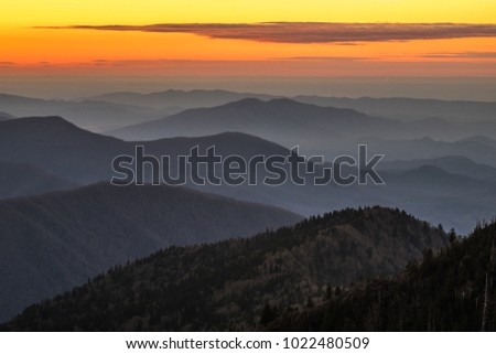 Sunset in the Great Smokey Mountain National Park. The sky is orange and yellow with a long, low cloud. The foreground is layers of mountains, hills, and ridges with barren trees in winter