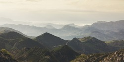 Sunset in the mountain natural landscape park. Valley on background dramatic sky and clouds. Panorama horizon view of scenery foggy hills Northern Spain alps. Travel mockup concept in evening time.