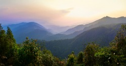 Sunset in the mountains of Northern Thailand. Mountains in the haze. Rainforest in the foreground. Doi Tung Mountain. Chiang Rai province. Thailand. Thai highlands