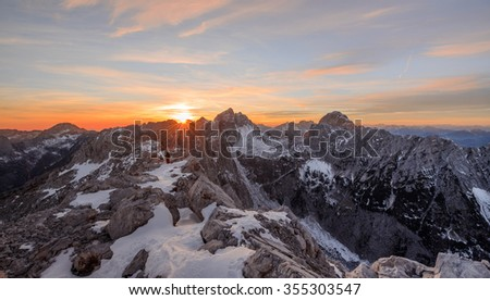 Sunset in the mountains with hikers resting at the top - Shutterstock ID 355303547