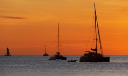 Sunset in the ocean with sailing catamarans in the background