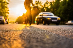 Sunset in the suburbs, the car and a bicycle traveling on the highway. Close up view from the asphalt level
