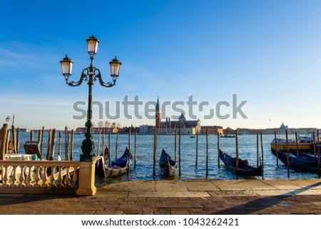 Sunset in Venice. Gondolas at Saint Mark's Square and church of San Giorgio Maggiore on background, Italy, Europe #1043262421