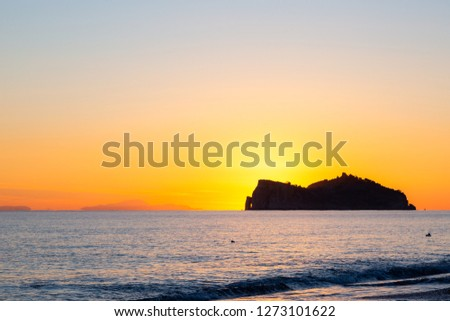 Sunset in West Turkish coast in Sarigerme village area with view on Baba Adasi isle. Calm clear sky with bright orange Sun behind montains