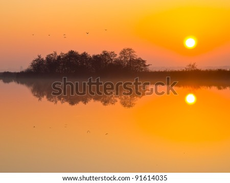 Sunset is reflecting in mirror like lake