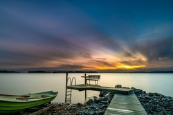 Sunset lake pier boat view. Pier sunset scene. Sunset pier lake water. Sunset pier landscape