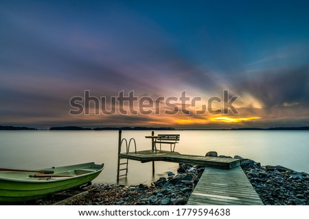 Photo of  Sunset lake pier boat view. Pier sunset scene. Sunset pier lake water. Sunset pier landscape