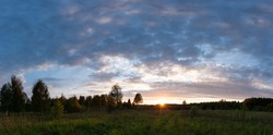Sunset landscape panorama of summer meadow with green grass in evening twilight under clouds on blue sky in bright sunset light, colorful panoramic view of field in sunset dusk with trees silhouette.