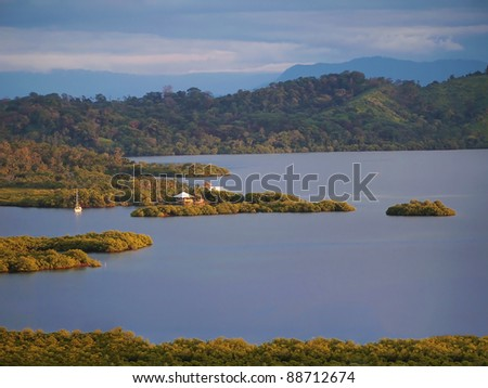 Sunset light over tropical coast with mangrove islands and a house, archipelago of Bocas del Toro, Caribbean sea, Panama, Central America