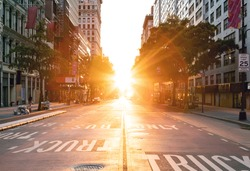 Sunset light shines over an empty view of 14th Street seen from Union Square Park in New York City NYC