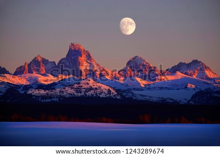Sunset light with alpen glow on Tetons Tetons mountains rugged with moon rising