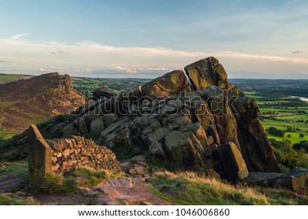 Sunset lights the heather and rocks at the Roaches in the Peak District National park. Hen Cloud can be viewed in the distance.