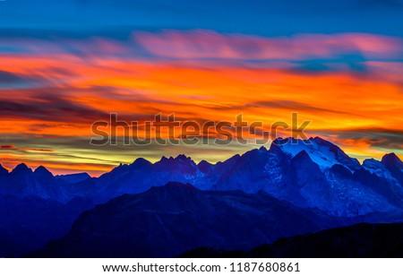 Sunset mountain peaks sky panorama. Mountain peaks sunset view. Sunset mountain peaks silhouette. Mountain sunset sky clouds
