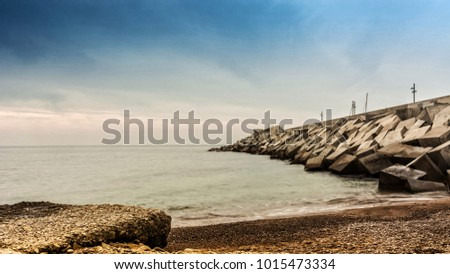 Sunset on a beach in Blanes, where you can see the wall breakwater of the port
