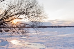 Sunset on a frozen river in winter