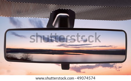 Sunset on a river, reflected in the rearviewmirror of a car