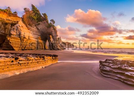 Sunset on a rocky beach in Taranaki district, New Zealand