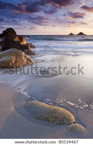 Sunset on a tranquil beach with Islands on the  Horizion. Porth Nanven Cornwall England UK