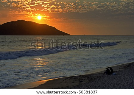 sunset on a tropical beach with a couple - stock photo