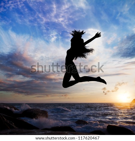 sunset on background beach with sea waves and long haired girl jumping