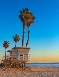 Sunset on beach with lifeguard tower and palm trees
