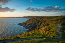 Sunset on Cornish cliffs, ocean and foot patch in wild scenery, English seascape