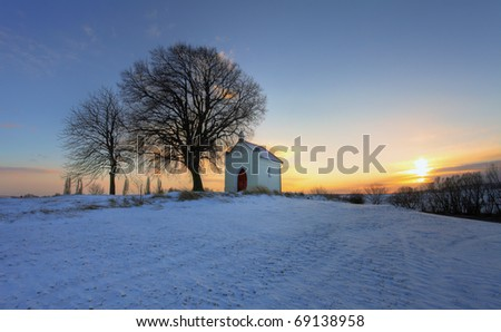 Sunset on frozen field with a chapel and clouds