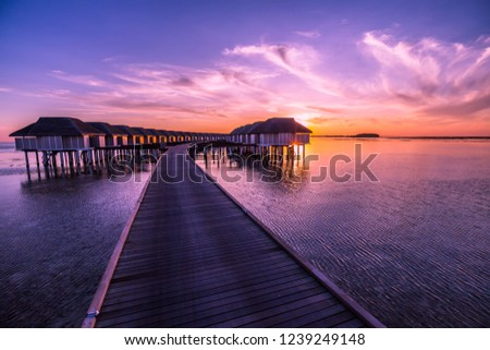 Sunset on Maldives island, luxury water villas resort and wooden pier. Beautiful sky and clouds and beach background for summer vacation holiday and travel concept