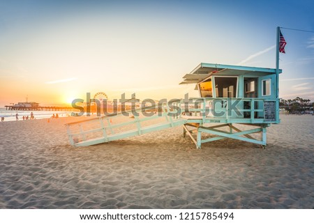 Sunset on Santa Monica beach with rescue cabin and amusement park on the background