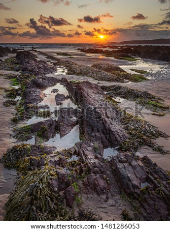 Sunset on scenic rocky beach in Freshwater West, South Wales, UK.Dramatic sky and red settlement rocks exposed during low tide and covered with seaweed.Beautiful coastline landscape scene.Nature.