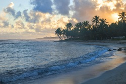 sunset on St. Croix with bright  blue ocean orange clouds and reflection in water