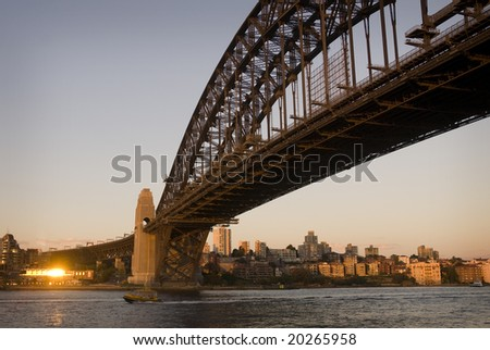 Sunset on Sydney harbour with water taxi passing below the Harbour Bridge
