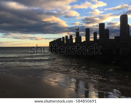 Sunset on the beach, silhouette of old pier and seagull perched on a wooden pylon.  Waves calming lap against the sandy shoreline of Coney island, Brooklyn, New York, USA. Stock fotó ©