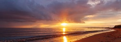Sunset on the beach. View of sea at sunrise. Sun fall down to sea making reflection on water. Bright horizontal landscape.