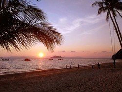Sunset on the beach with palm tree leaf, palm trees and swing silhouette with clouds in the sky, people on the beach and boats on the horizon. Sunset scenery on tropical island in Thailand.