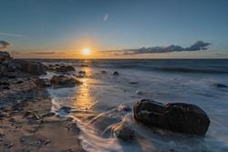 Sunset on the beach with sand und stones, sunset over sea, sunset on the cliffs at Heilgenhafen, Schleswig-Holstein, Germany