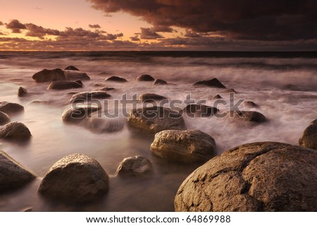 Sunset on the coast of the Baltic Sea. A combination of pictures from water exposures with different shutter speeds: short and long.