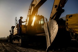 Sunset on the construction site. Silhouette of a contractor builder is sitting near bulldozer. Construction machinery concept