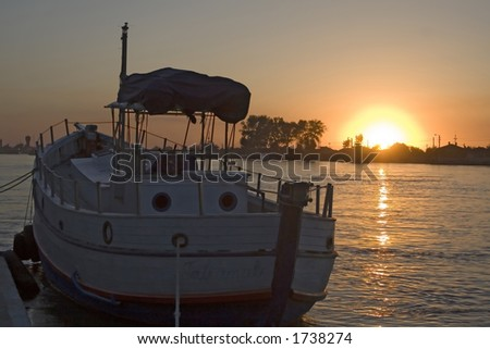 Sunset on the Danube river and boat silhouette