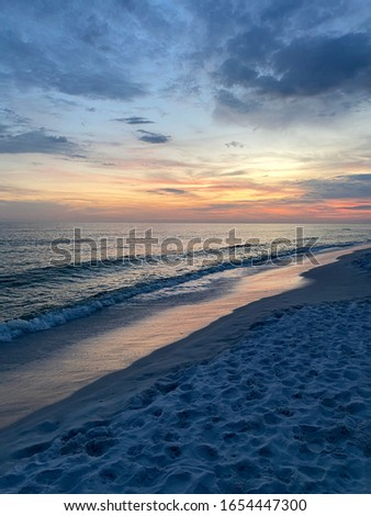 Sunset on the Gulf of Mexico with colorful skyline and gray clouds