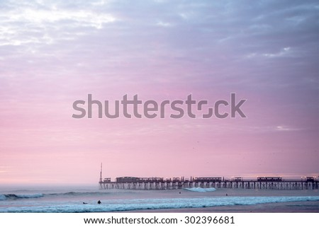 Sunset on the Pacific Ocean, the sun breaks through the mist and famous pier at Pimentel. Peru, Latin America