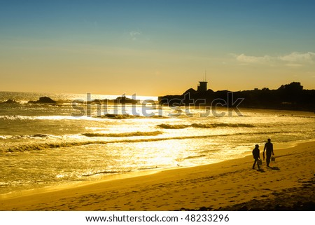 Sunset on the Pacific Ocean while a couple walk on the Malibu beach in California