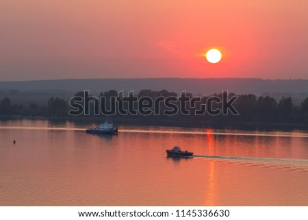 Sunset on the river Kama. The sun sets. The river transport is finishing its working day. #1145336630