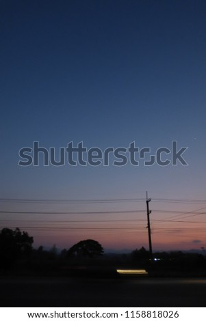 Stock Photo Sunset on the road side in rural Northern Thailand province of Tak with trail of vehicle light and electrical pole.