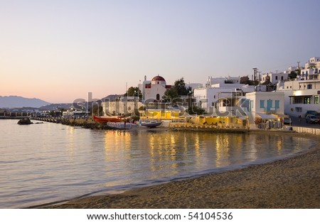 Sunset on the sea near the island of Mykonos in Greece and the night lights of restaurants and churches on the beach ...