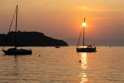 sunset on the sea with sailboats and islad silhouette ,