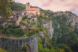 Sunset or sunrise view of the scenic hilltop medieval French village of Saint-Cirq-Lapopie, France with the fortified church illuminated above the Lot River.