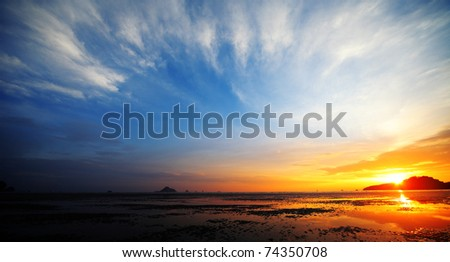 Sunset over a beach during low tide