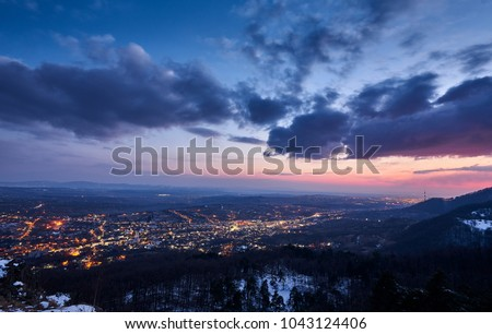 Sunset over a city. The sky is colorful and full of clouds.