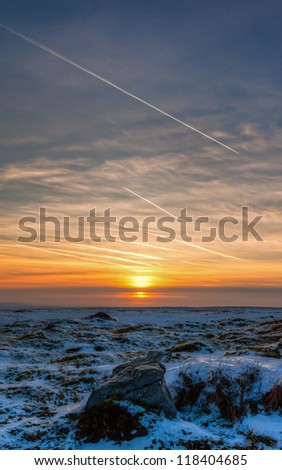 Sunset over a cold snow covered moorland in the middle of winter